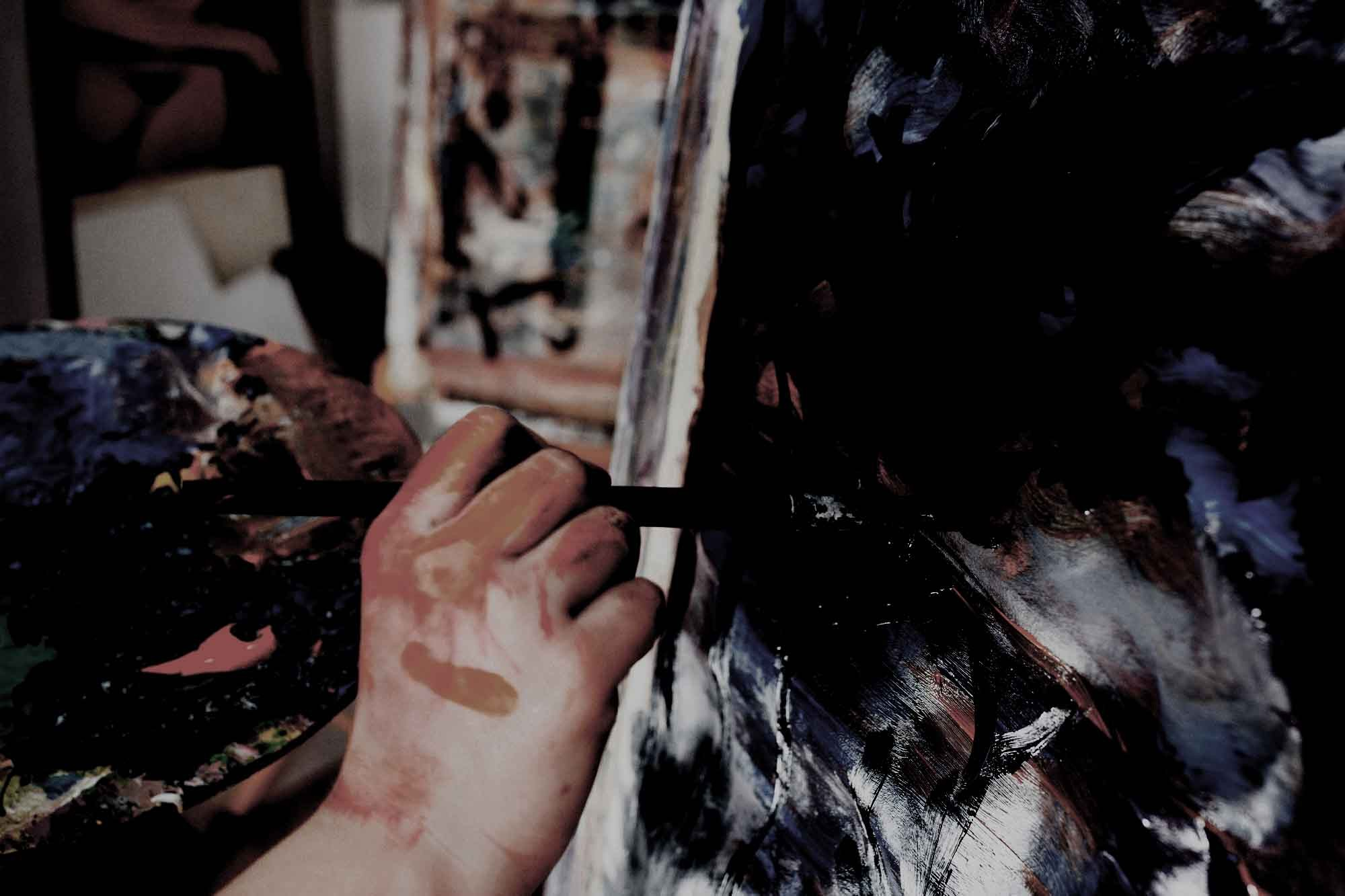 artist-s-hand-painting-with-black-brushstroke-canvas_copy1.jpg